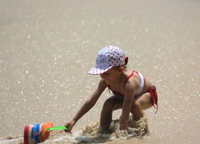 niña con gorrito jugando en la playa con balde