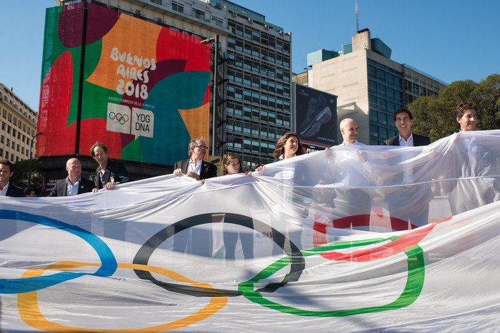 personas con bandera de juegos olímpicos