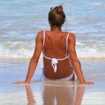 Mujer sentada en la orilla del mar