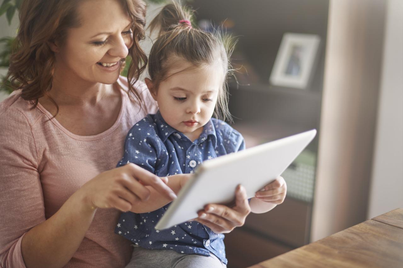 Madre sonríe con hija miran tablet