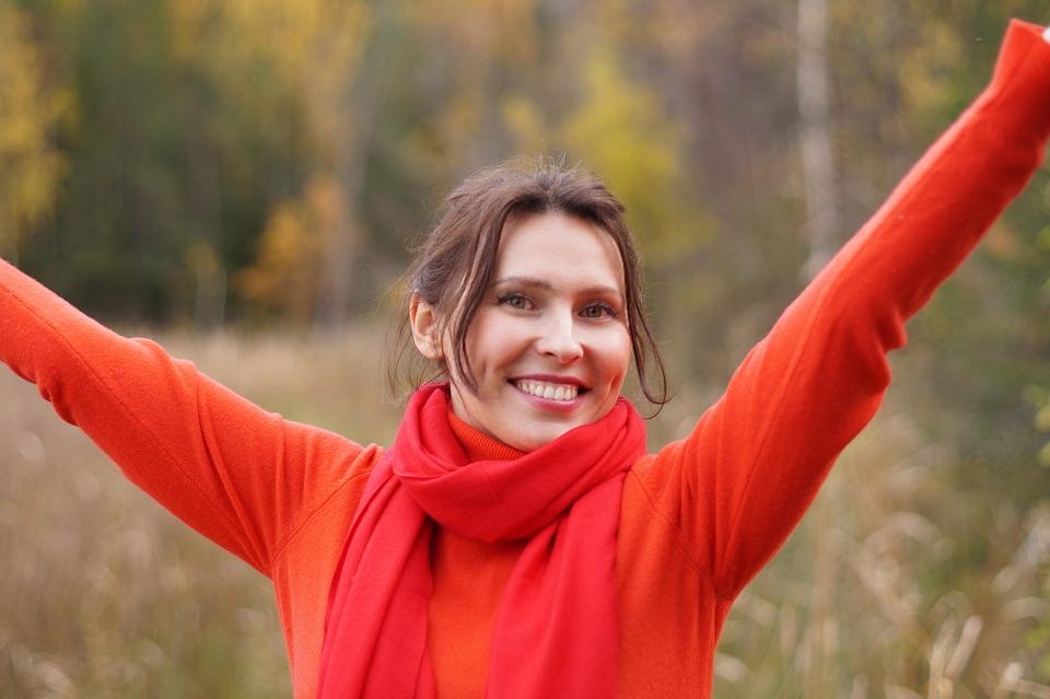 mujer joven feliz extiende brazos en otoño