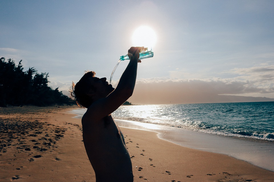 Hombre tomando agua en una playa