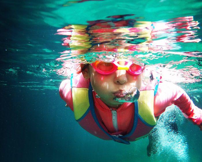 niña nadando en pileta