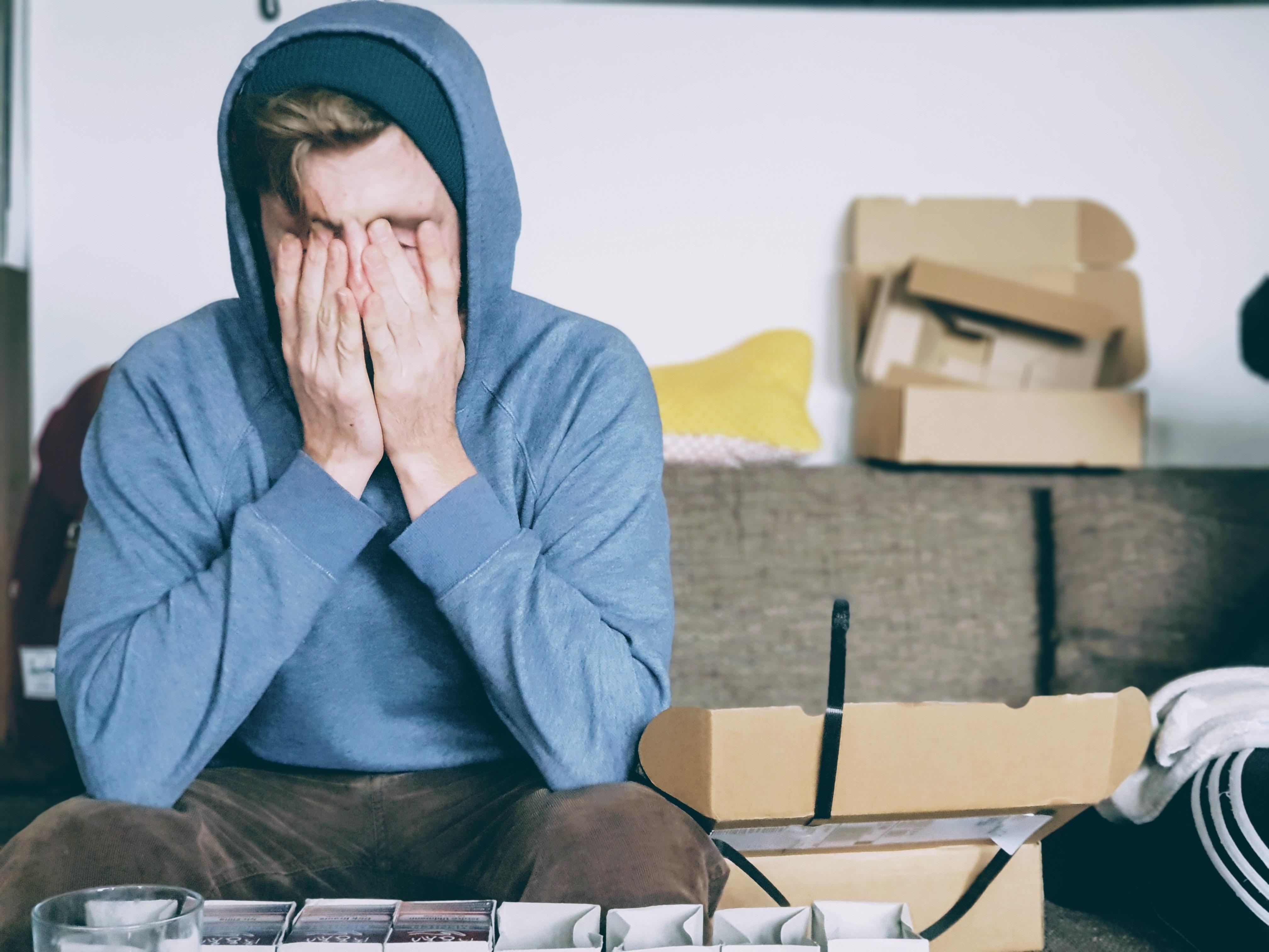 hombre con capucha triste preocupado se tapa rostro con las manos