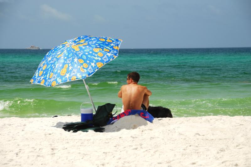 hombre en la playa en traje de baño junto a sombrilla