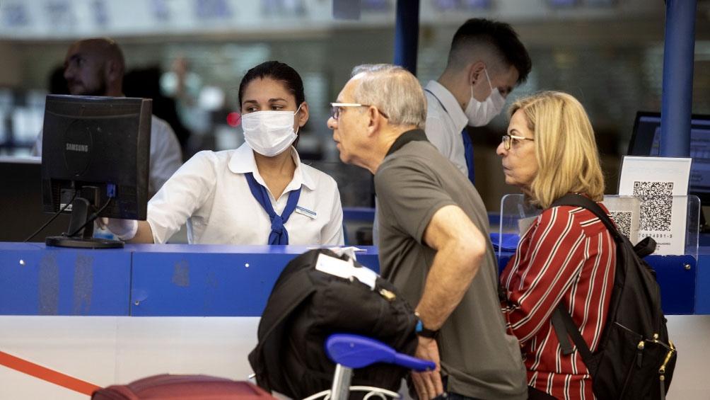 Personas con barbijo en aeropuerto