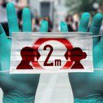manos con guantes sosteniendo cartel sobre coronavirus