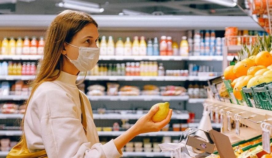 mujer con barbijo comprando alimentos durante la pandermia