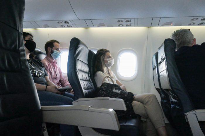 Mujer en asiento de avión con barbijo