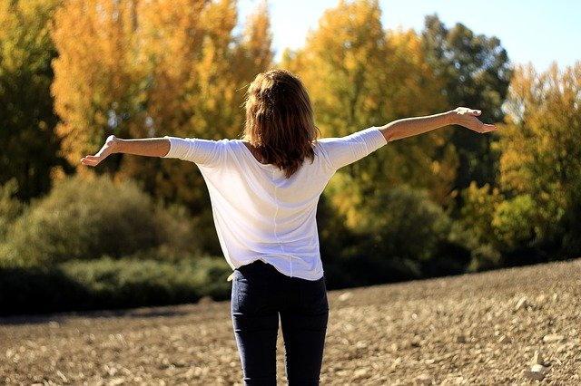 mujer con brazos abiertos al aire libre