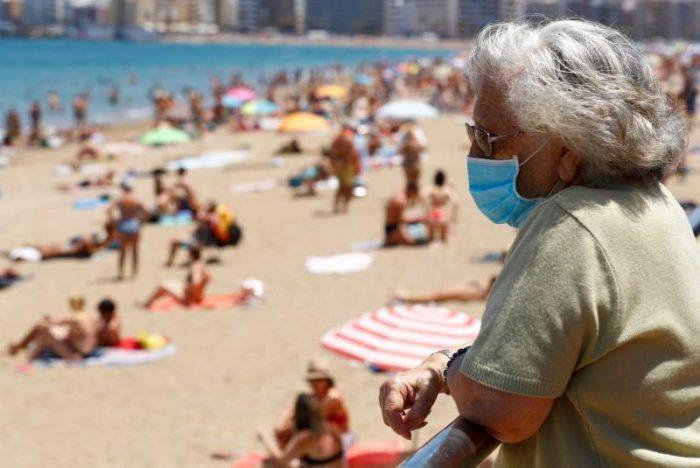 mujer en la playa con barbijo