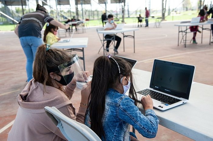 clase de computación al aire libre maestra y alumna con máscara
