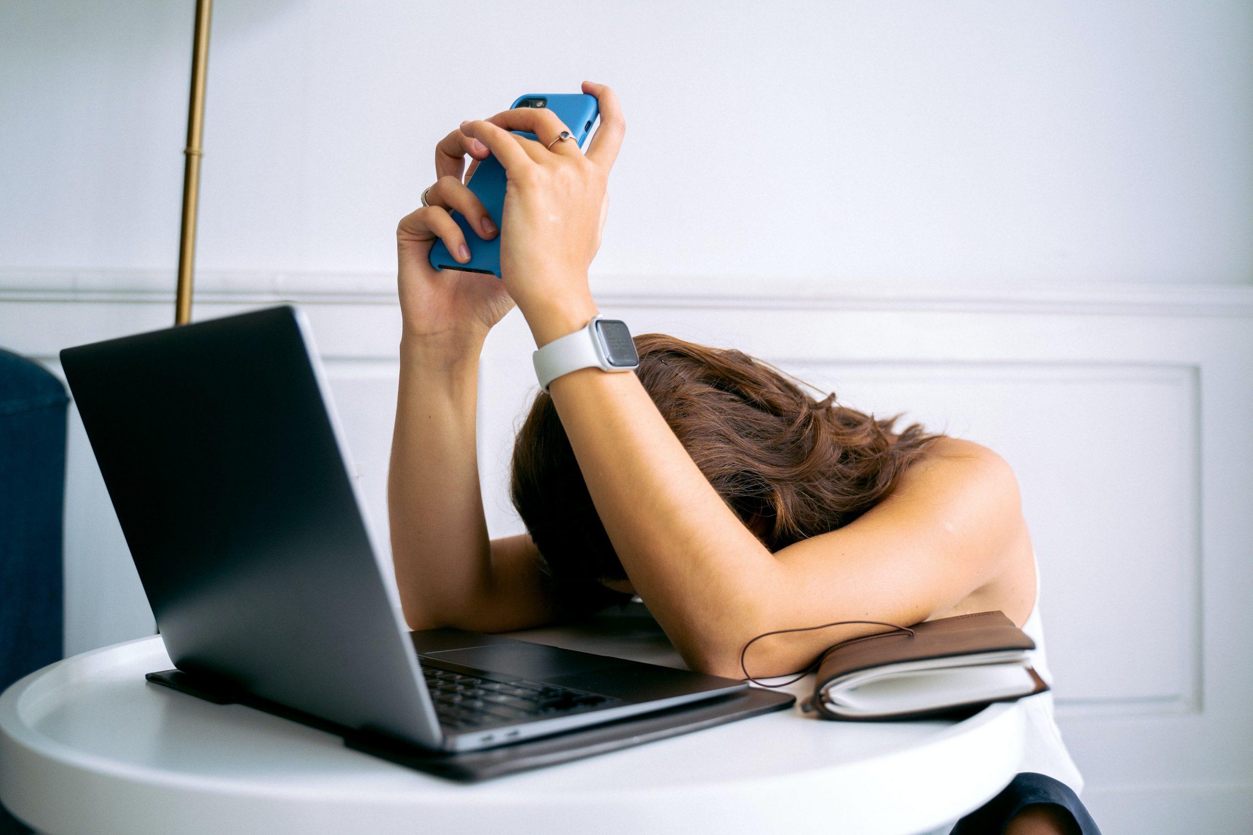 mujer cansada con computadora y celular